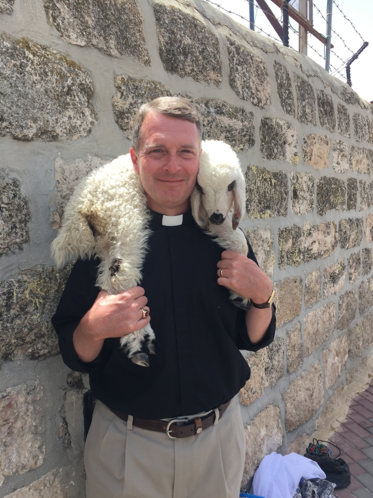 In his Sunday attire, the Rev. Jeff Miller stops to pose with a lamb.